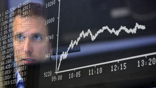 Trader sit at his desk under the day's performance board that shows a dive in the value of the DAX index of companies at the Frankfurt Stock exchange